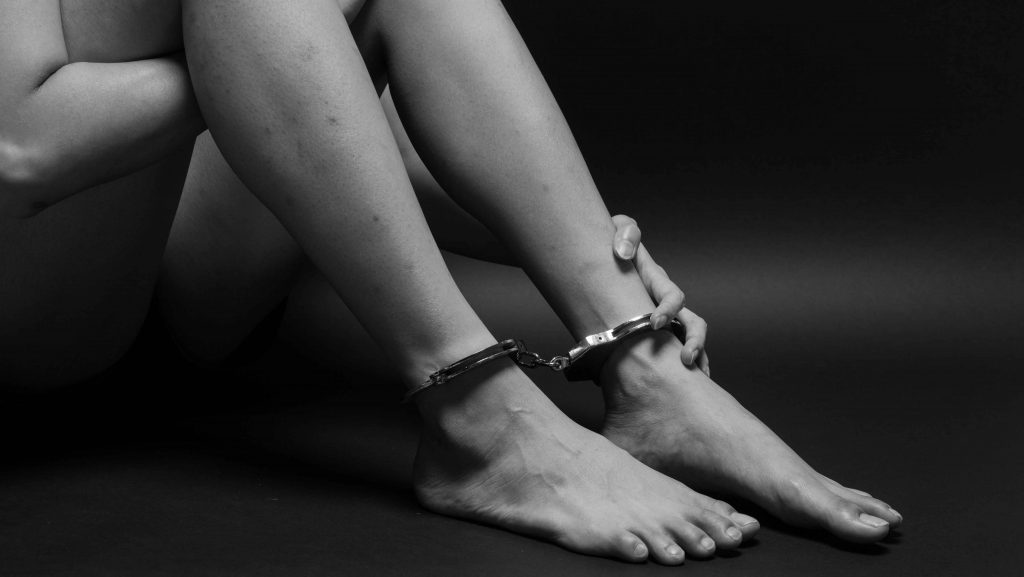 concept human trafficking,hand girl in shackle on isolate black background